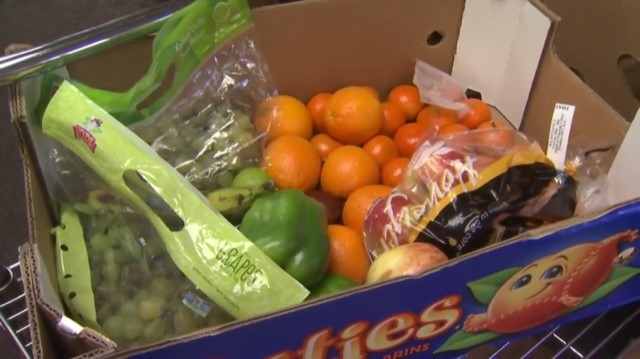 Closeup image of a cardboard box with fresh oranges and peppers inside.