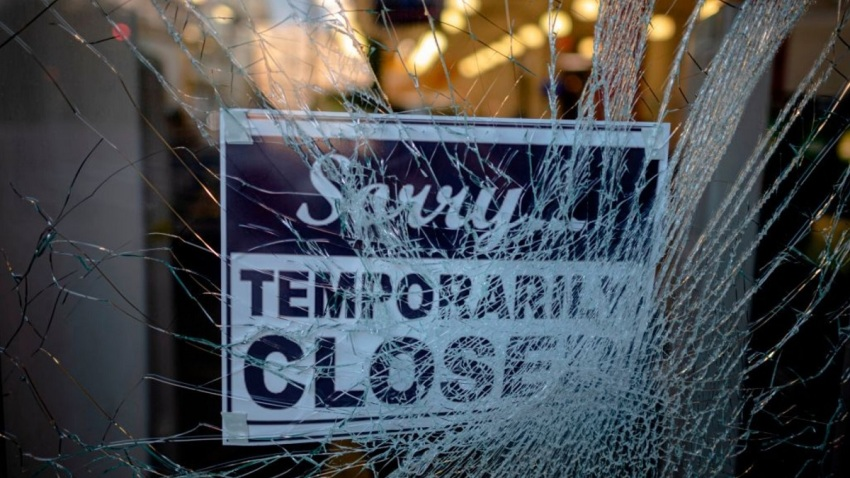 "A broken window with a sign hanging that reads ""Sorry temporarily closed."""