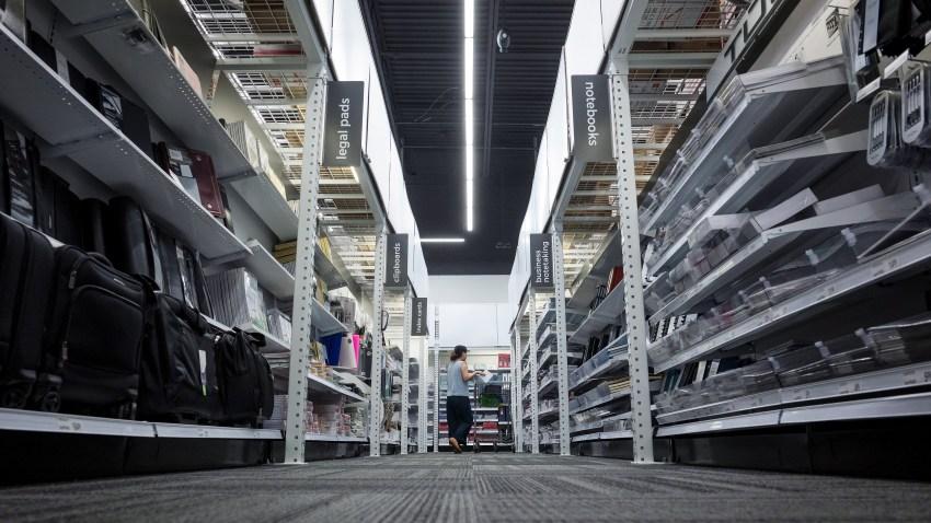 A customer pushes a cart through an Office Depot store.