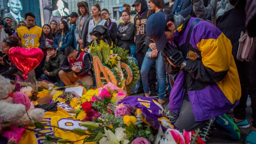 People gather around a makeshift memorial for former NBA and Los Angeles Lakers player Kobe Bryant after learning of his death, at LA Live plaza in front of Staples Center in Los Angeles, Jan. 26, 2020.