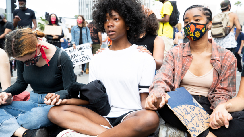 Demonstrators sit holding hands during a march in response to George Floyd's death on June 2, 2020 in Los Angeles.