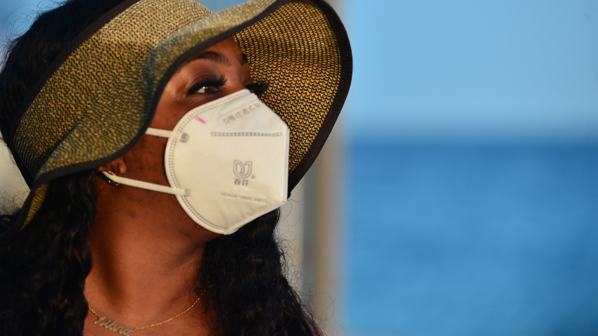 A beach-goer wears a face mask on the beach after a mandate to wear face masks in public spaces went into effect on Tuesday June 30, 2020 in Miami Beach, Florida