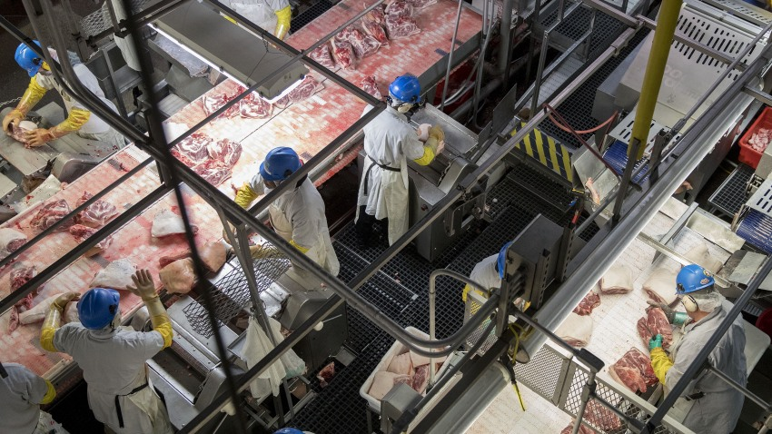 In this April 12, 2017, file photo, employees butcher pork at a Smithfield Foods Inc. pork processing facility in Milan, Missouri.
