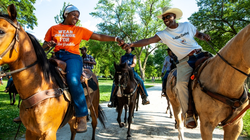 Two black riders on horseback fist bump in front of some trees
