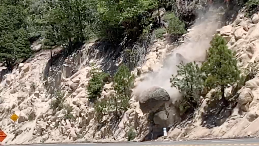 A boulder is removed from a hillside off Highway 18 in the San Bernardino Mountains
