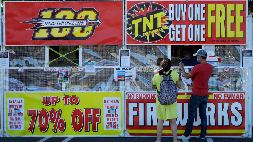 People purchase fireworks on Thursday, July 2, 2020, in Dublin, Calif. For many Americans, the Fourth of July won't be about big festivities but setting off fireworks themselves. Hundreds of cities and towns have canceled shows Saturday because of the coronavirus pandemic, and sales of consumer fireworks are booming; though officials are concerned about fires and injuries with more pyrotechnics going off in backyards and at block parties.