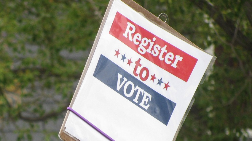 Una persona muestra un cartel para registrarse a votar.