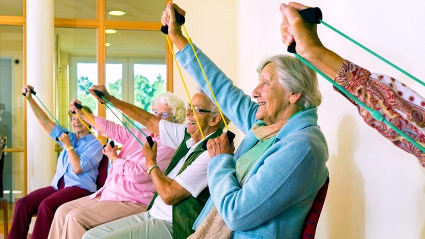 Adultos mayores haciendo estiramientos sentados.