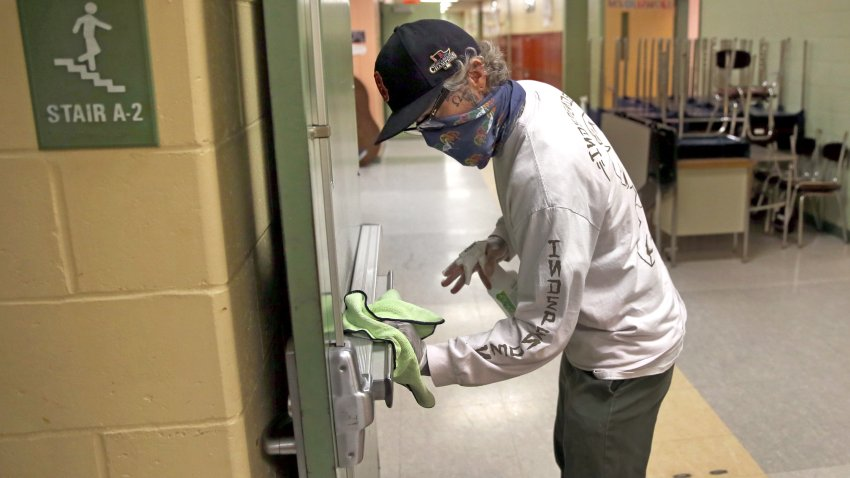 A custodian wipes down a hallway doorway at the Mildred Avenue K-8 School building in Boston's Mattapan and for the reopening of school on July 9, 2020.