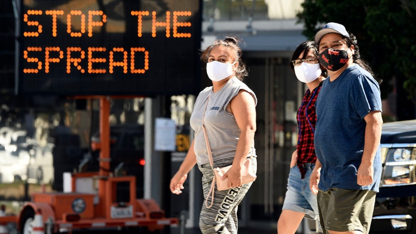 Pedestrians in masks walk in front of a sign reminding the public to take steps to stop the spread of coronavirus, July 23, 2020, in Glendale, Calif.