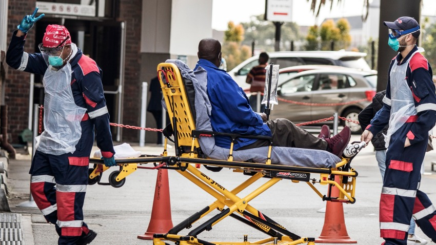 In this July 10, 2020, file photo, an emergency paramedic wearing full COVID-19 coronavirus personal protective equipment (PPE) flashes the victory sign as they arrive with a patient at the Greenacres Hospital in Port Elizabeth.