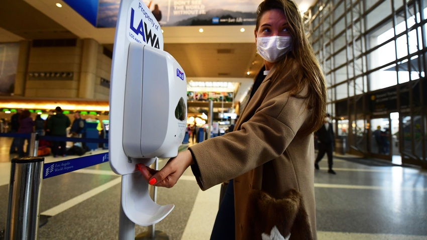 A woman wearing a facemask uses hand sanitizer on arrival at LAX.