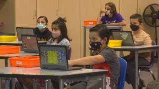 Children wear masks while sitting in a classroom