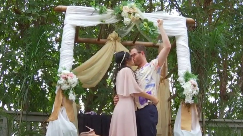 A couple kisses at an altar