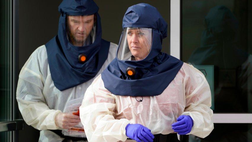 Salt Lake County Health Department public health nurses look on during coronavirus testing outside the Salt Lake County Health Department in Salt Lake City