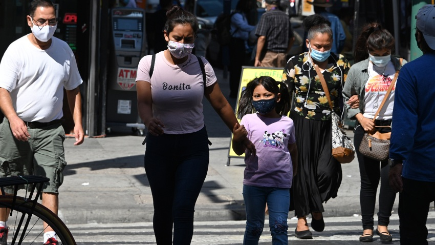 People wearing masks walk on a street in downtown Los Angeles.