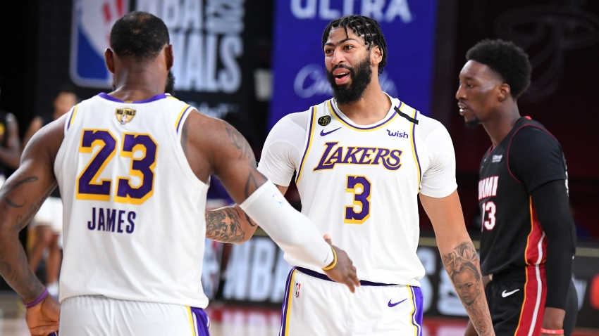 In this Oct. 11, 2020, file photo, LeBron James #23 of the Los Angeles Lakers and Anthony Davis #3 of the Los Angeles Lakers high five during the game against the Miami Heat during Game Six of the NBA Finals at The AdventHealth Arena at ESPN Wide World Of Sports Complex in Orlando, Florida.