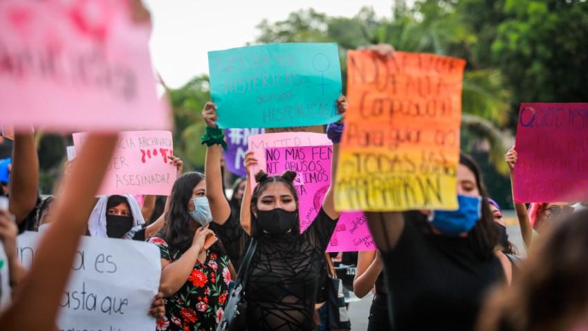 Grupo de mujeres muestran carteles de protesta