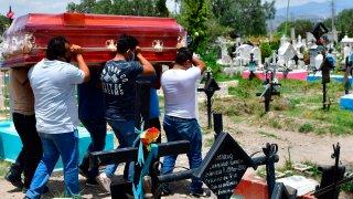 Hombres cargan un féretro en un cementerio.