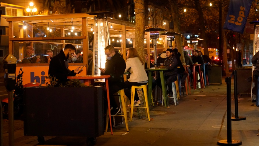 People sit in an outdoor dining area on Market Street amid the coronavirus outbreak in San Francisco, Tuesday, Nov. 24, 2020.