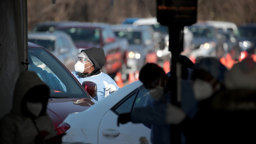Workers test residents at a drive-up COVID-19 test site on November 13, 2020 in Aurora, Illinois.