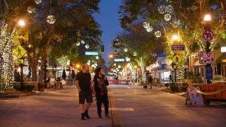 Two people walk down the main shopping and dining street in Burbank.