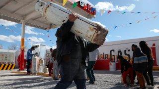 Personas hacen fila para cargar cilindros de gas