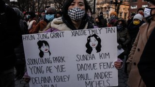 A person holds a sign with the names of the people who died at a peace vigil to honor victims of attacks on Asians