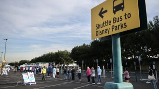 People wait in line to receive the COVID-19 vaccine at a mass vaccination site in a parking lot for Disneyland Resort.