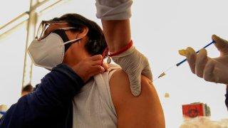 Una mujer recibe una vacuna en el brazo izquierdo