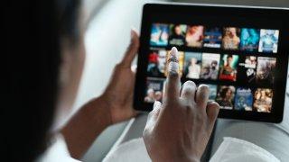 Mujer revisa una página de un servicio de streaming de películas y series.