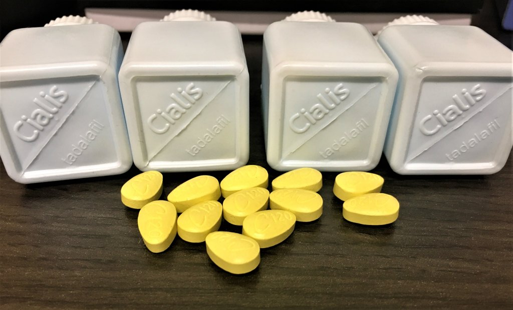 """Neon green pills sit scattered on a table, in front of four plastic bottles that read """"Cialis."""" The pills are counterfeits seized by U.S. Customs and Border Protection."""