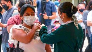 Una enfermera aplica una vacuna a una mujer migrante en Tijuana