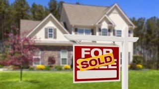 Señal de vendida en letrero frente a una casa unifamiliar.