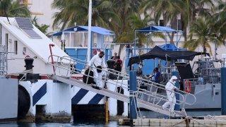 Peritos forenses vestidos de blanco recuperan tres cuerpos del mar