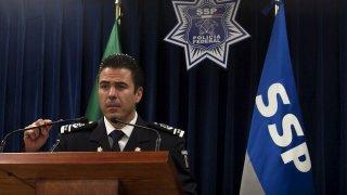 Exjefe policial mexicano, detrás de un atril. Viste uniforme policial y está rodeado de insignias y banderas