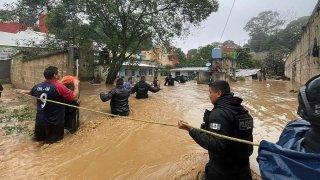 Hombres caminan por una calle inundada