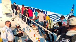 migrantes haitianos suben las escalerillas de un avión