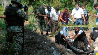 Peritos forenses trabajan en una fosa clandestina