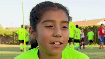 Una niña que juega el fútbol con mucho amor