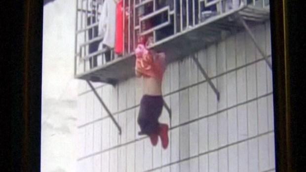 Captan sensacional rescate de niña colgando de edificio