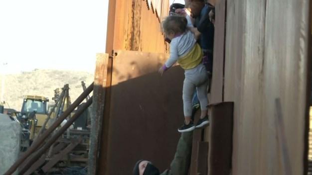 Desgarrador: familia migrante salta el muro con niños