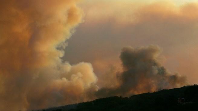 Evacúan a miles por incendio forestal